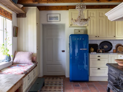 Ann brukar alltid ha blå kylskåp i sina kök, detta är från Smeg. Köket är byggt av Ikeastommar med luckor från Lillaforssnickeriet i Degeberga efter en modell från Marbodal. Den väggfasta bänken är populär att ligga på och är klädd med en matta