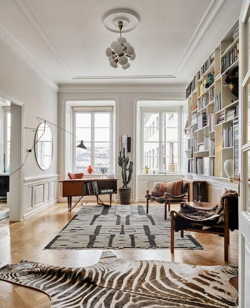 Med de flesta detaljer samlade i bokhylleväggen blir arbetsrummet både luftigt och inspirerande. Den som här väljer att jobba hemma får sitta på Arne Jacobsens stol Sjuan i rött skin och omges av än fler desingklassiker, bland annat Arne Norells safaristolar Sirocco.