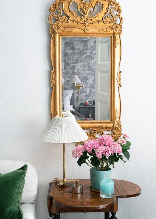 Den antika spegeln med guldram räddade Gittan från förfall och restaurerade själv. Bordet med intarsia är ett gammalt ärvt spelbord. En turkos blomkruka passar fint till ljuslyktan i samma färg, Skogsberg & Smart.