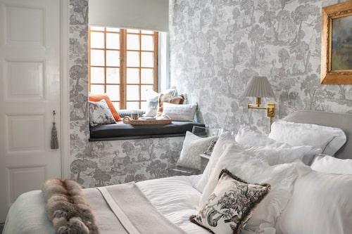 Tapeten Versailles i grått finns på sovrummets alla väggar, Cole & son. Sänggaveln har Gittan sytt själv, liksom alla kuddöverdrag.