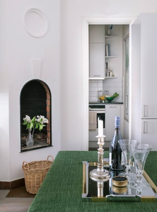 Den öppna spisen är pyntad med blommor i en glaskaraff. I det lilla köket lagas mycket mat, som serveras på matbordet i vardagsrummet.
