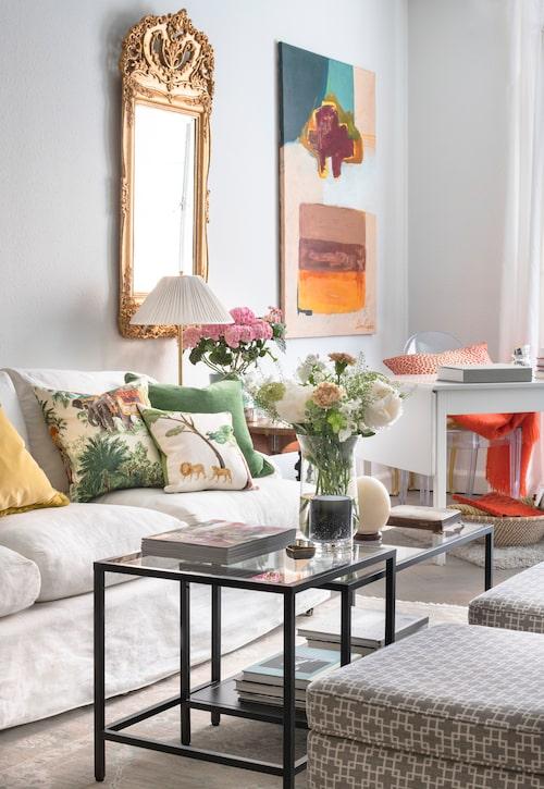 Vardagsrummet är smalt, och att lämna väggen fri från dekor rakt ovanför soffan gör intrycket luftigare. Puffarna är klädda i tyg från Romo.
