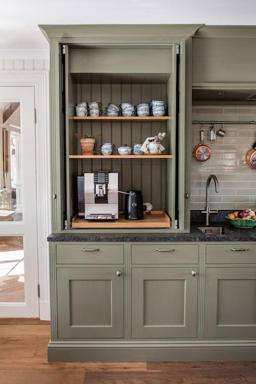 Så kallade pocket doors, dörrar som skjuts in i sidorna vid öppning, var ett av Madeleines önskemål. I detta skåp står hennes favoritpryl i köket, kaffemaskinen.