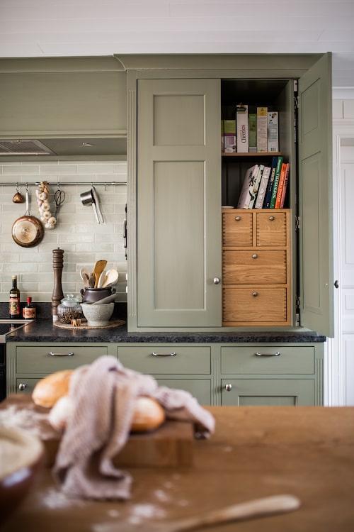 Innanför dörrarna syns sinkade lådor i oljad ek och tidstypisk pärlspont klär skåpens insida. Här förvaras kryddor och kokböcker på armlängds avstånd.
