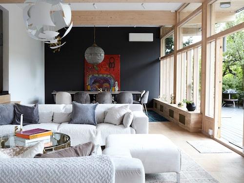 """Ena väggen i vardags-rummet består av idel fönster och en utgång mot terrass och pool. Soffor från Zanotta, omklädda i tyg från Designer's guild. Taklampan i förgrunden, i form av en trasig glödlampa, är från Northern. Över det måttbeställda matbordet i champagnefärgad betong hänger en taklampa från Kabusa design factory. Tavlan är målad av konstnären Peter Wahlbeck, en vän till familjen. """"Just denna tavla ringer Peter årligen om, och vill köpa tillbaka!"""""""