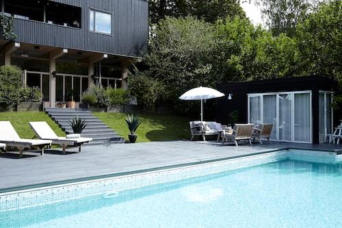 Sluttningen mot poolområdet är täckt med konstgräsmatta. Terrassen är ommålad i ljusare ton, tidigare var den svart. Utemöbler från Formlagret.