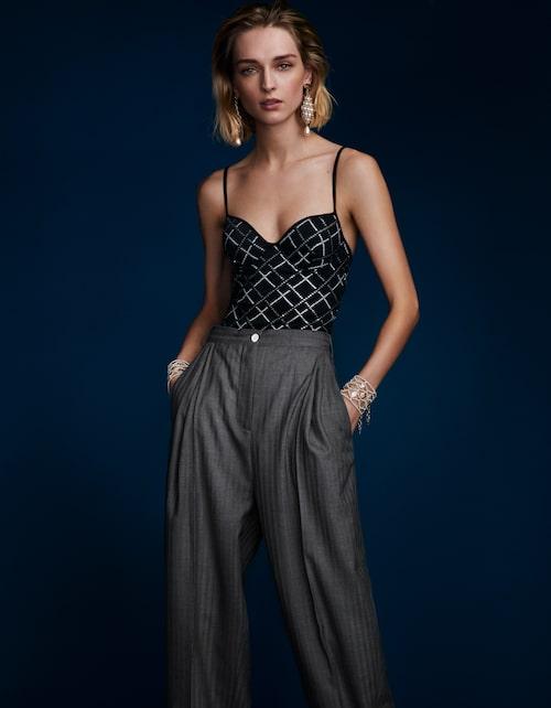 Baddräkt av glittrig jersey, 16800 kr, Chanel. Kostymbyxor av ull, 5700 kr, Acne Studios. Örhängen med pärlor av metall/harts, 13000 kr, och armband av metall/glas/strass, 31800 kr, allt Chanel.