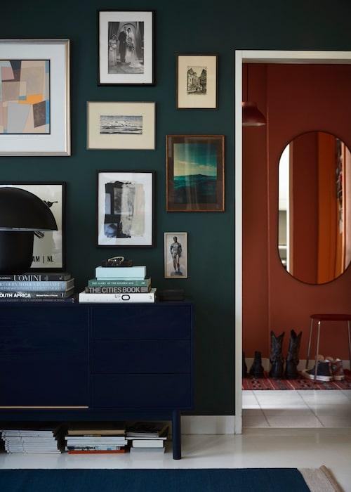 Sideboard i mörkblått från Bolia, och ovanför det hänger en samling loppis- och auktionsköpt konst blandat med konstaffischer från Artilleriet. Den bulliga bordslampan är Carl Johan mini, Olsson & Jensen. I hallen intill, lampa och pall från Hay, spegel, Ikea, och matta köpt i Marrakech.