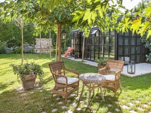 Rottingmöbeln fraktade Yvonne hit från Sika design, liksom lyktorna från Ekerö möbler. Något parasoll behövs inte eftersom grenarna tyngs ner av små lod för att skugga bättre. I bakgrunden syns trädgårdens evigt porlande springbrunn.