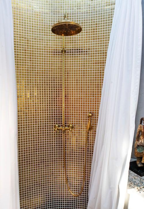 Guldmosaiken i duschen kommer från italienska Bisazza, och duschstången som håller draperiet uppe är rund förstås.