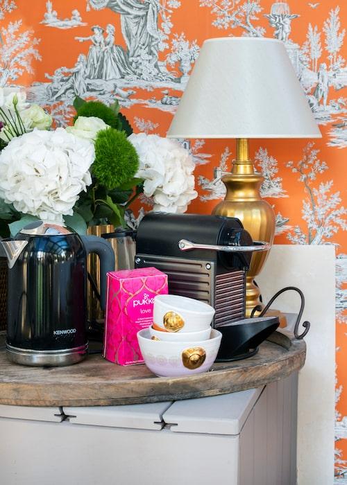 När gästerna vaknar på morgonen kan de precis som på ett bättre hotellrum brygga sitt eget kaffe och te. Lampan på guldfot är från Oscar & Clothilde och kopparna från Charlotta Unger.