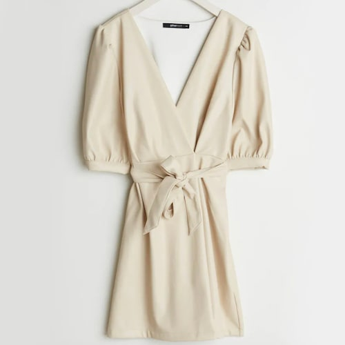 Omlottklänning i cremefärgat fuskskinn från Gina Tricot. Klicka på bilden och kom direkt till klänningen.