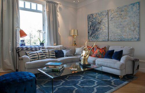 """Tavlorna och kvinnoskulpturen i """"det blå vardagsrummet"""" är gjorda av Saras vän, konstnären Caroline Tamm. Guldlampa från Kartell och matta från Layered."""