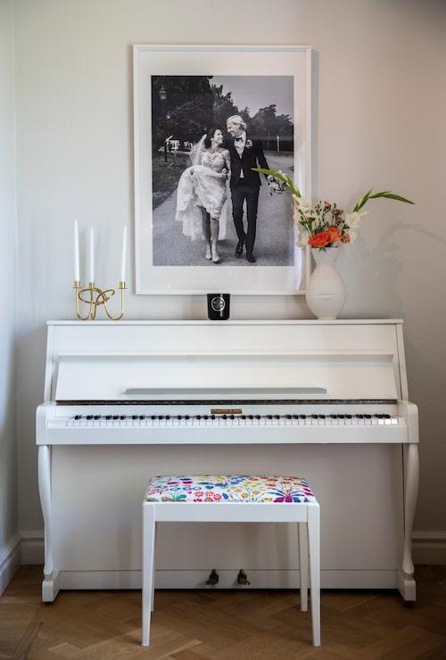 Över pianot hänger ett stort bröllopsfoto taget av fotografen Kate Gabor.
