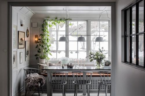 Den vackra glasverandan är en ljus plats att tanka lugn-och-ro-känslor på, året om. Matbordet är specialbeställt och har en skiva med likadan grönmelerad granitsten som de i bänkskivorna i köket intill. Stolar, R.o.o.m. Takpendel, Muuto, och i fönstret en munblåst klusterlampa, Tadé. Småvaserna kommer från Lindholm och H&M Home, som även har den klotrunda glasvasen. Ljusstakar, Bolia.