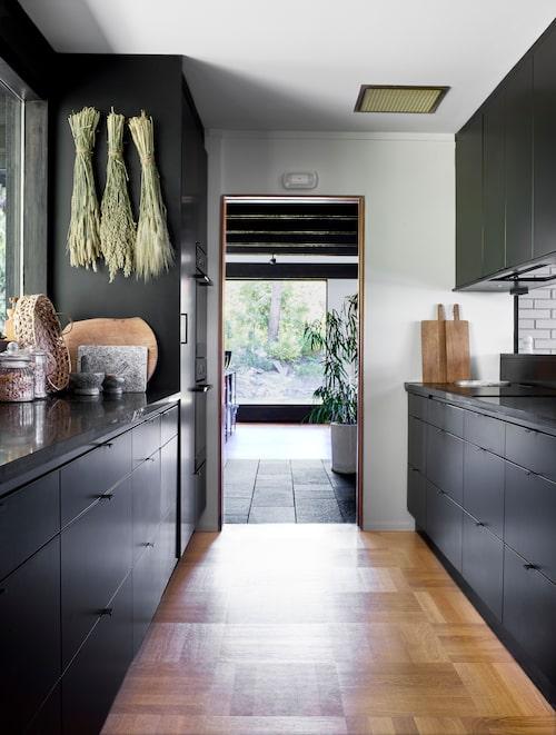 Svart kök från Vedum. På golvet nylagd parkett som harmonierar med ett liknande originalgolv i vardagsrummet som har panoramafönster i fonden.
