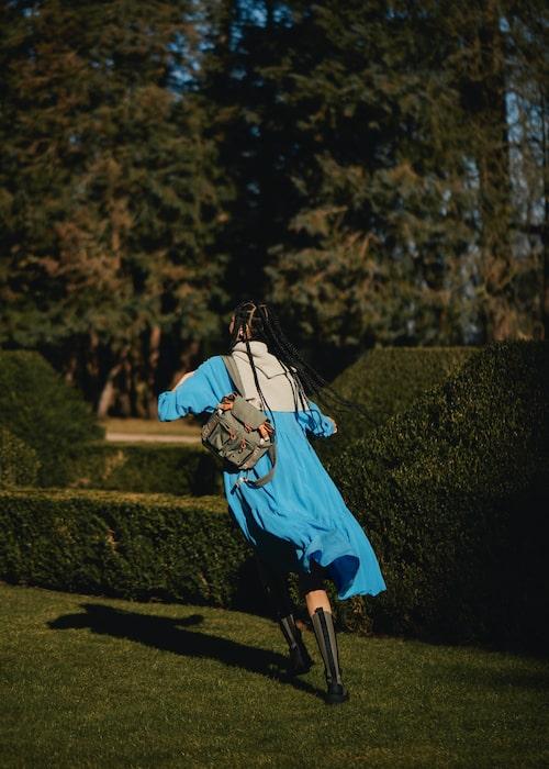 Klänning av lyocell, 890 kr, Arket. Stickad tröja av ull, 1 800 kr, Filippa K. Ryggsäck av nylon, 1 695 kr, Ganni. Stövlar av skinn, 4 595 kr, Ganni.
