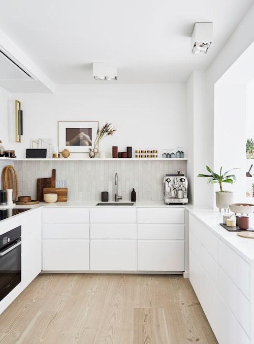 Enkelt vitt kök från Ikea toppat med skivor av vit corian. Stänkskyddet över diskbänken är cementkakel från Marokk satt på höjden. Fotot på väggen är från Kristina Dam studio, liksom keramikskålarna på fötter.