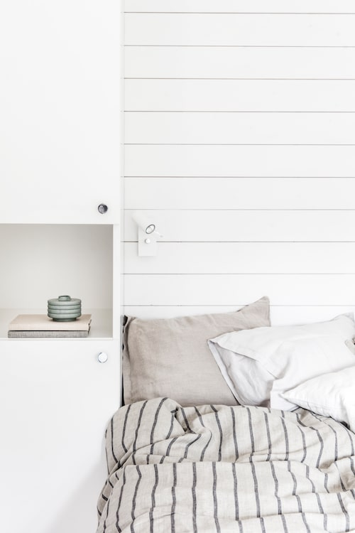 Att sätta garderoberna på samma vägg som sängen och måla in i samma färg ger en lugnare känsla än att ha de utspridda. Randigt påslakan i linne från Lovely linen. Beige påslakan, ljusgrått örngott och beige pläd, allt från Himla. Vitt örngott från Ikea, offwhite pläd med fransar från Granit, anteckningsböcker från Bookbinders, design och grön räfflad cylinderformad vas från Lindform.