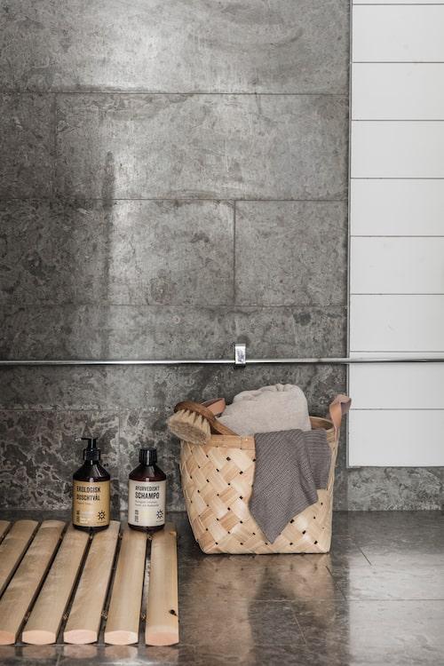 Väggen i duschen är klädd i kalksten. Korg från Åhlens, tvättlapp från Granit, beige badlakan från Himla. Badborste, ayurvediskt schampo, ekologisk duschtvål och badrumsmatta i trä, allt från Iris hantverk.