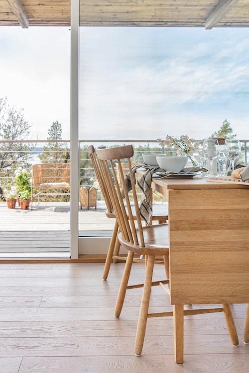 Utsikten från matbordet är hänförande och terrassen utanför blir ett extra rum. Slagbordet kommer från numera nedlagda R.o.o.m. Pinnstolarna Lilla Åland av Carl Malmsten är köpa begagnade.