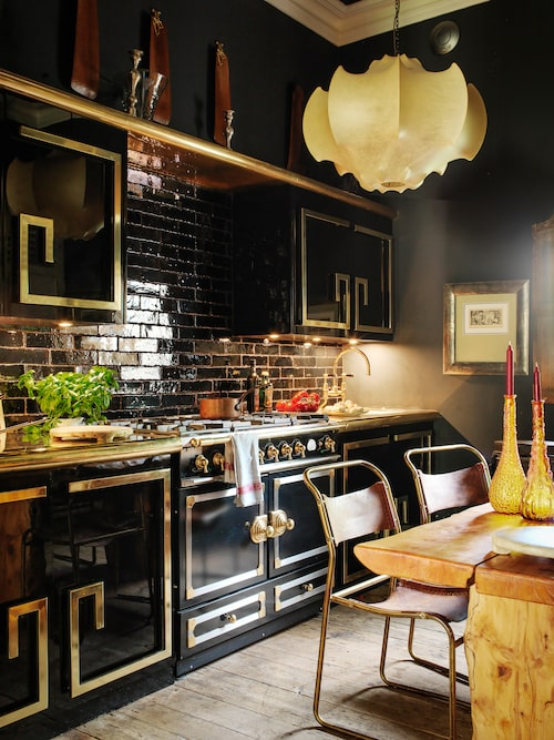 """Det här köket är ett praktexempel på trenden """"Mycket av allt"""". Svart och guld har ansetts som på gränsen till smaklöst, men inte längre. Här har köksinredningen en asiatisk touch, tanken går till kinesiska skåp och blanka lackaskar. Den extrabreda gasspisen som matchar mönstret på luckorna är från franska lyxmärket La Cornue. Lampan är Achille Castiglionis designklassiker Viscontea som inte är asiatisk men har drag av pagodform. Svart glänsande kakel fullbordar det hela."""