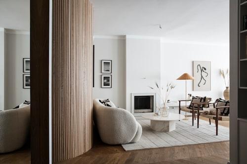 """När man kommer in i vardagsrummet från den avlånga hallen möter den rundade väggen mot sovrum och badrum. """"Vi har byggt in öppna spisen för att få en annan känsla. Den ser maffigare ut nu. Bänken till höger har vi byggt också"""", säger Elin Skoglund. Soffa från Sofa company, golvlampa och bord, båda från Gubi, stolar, Dusty deco för Nordiska galleriet, matta Nordic knots. Väggarna i vardagsrum och kök är målade med kulören Sommarsnö från Jotun."""