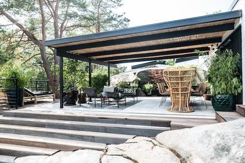 Paret har gjutit en ny grund för uteplatsen och lagt en ljus klinker som smälte fint ihop med stengolvet inomhus. Undertaket i den stora pergolan är klätt med bambu och runt terrassen löper trappor som knyter ihop de olika delarna av naturträdgården.