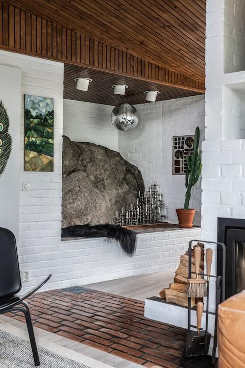 En del av berget som huset är byggt på skjuter in i vardagsrummet på ett effektfullt sätt. Här kombinerat med bling från discoboll och en försvarlig samling Nagelljusstakar.