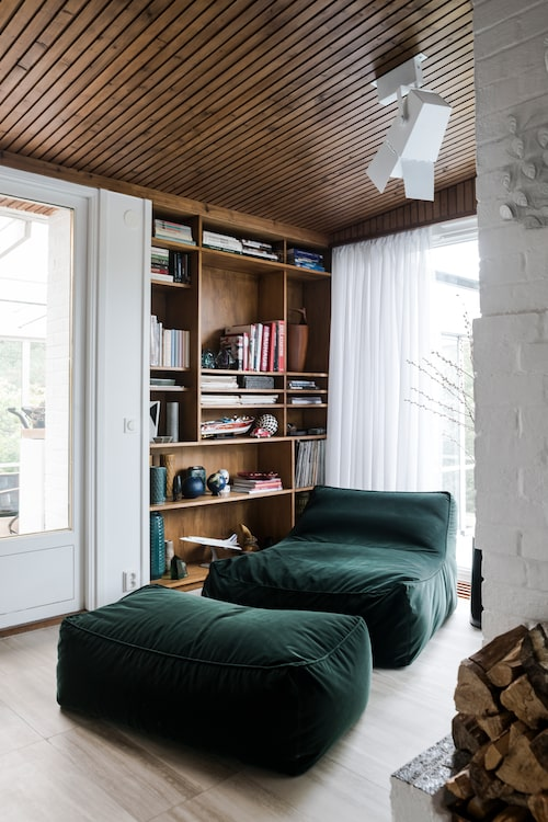 I ena kortändan av vardagsrummet, bakom den öppna spisen, ligger läshörnan. Den platsbyggda hyllan i teak är i original. Liggfåtöljen Zoe med fotpall i grön sammet från italienska Verzelloni.