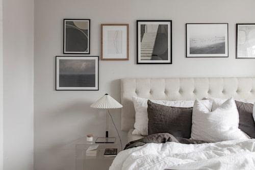 I Puttes och Johannas mysiga sovrum hänger tavlorna på rad ovanför sänggaveln, från Ellos. Sängkläder från H&M home, nattduksbord, Zara home och lampa, Hay