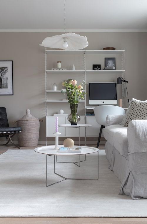 I det nedre vardagsrummet syns brickbord från David design, Stringhylla och kontorsstol från Hay. Lampa från Globen lighting och soffa från Ikea.