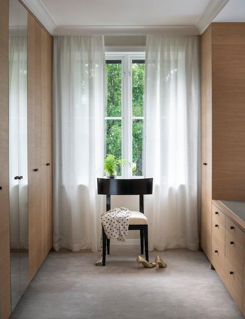 Annicas dressingroom har skåp på båda sidor klädda i ek. Den heltäckande mattan är densamma som i sovrummet. Skira linnegardiner ger ett mjukt ljus, och vid fönstret står en svartmålad stol från Attila Suta.