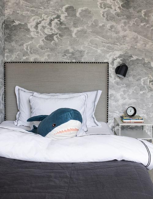 I sonens rum är väggarna klädda med tapeten Nuvolette från Fornasetti, sänggaveln med nitar runt ramen är specialtillverkad hos In Your Dreams. Sängkläder från H&M Home Collection.