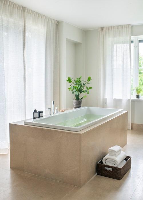 Badkaret står fritt mitt i badrummet och skapar en lyxig spakänsla. Golv och badkarssidor av kalksten från Stenfirma Bror Törner. De skira gardinerna med tvärrandig struktur är från spanska Lizzo/Mariana Madero agenturer.