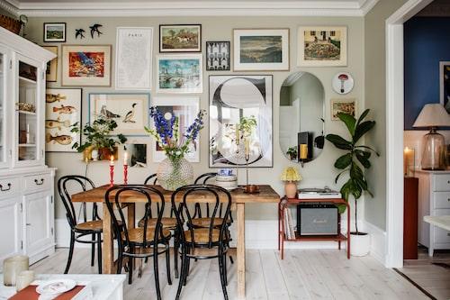 Sebastian älskar att inreda och målar gärna både väggar och möbler. Vardagsrummet är målat i kulören Duva från Alcro, i läcker kontrast skymtar den blå hallen till höger. På väggen samsas loppistavlor med keramikföremål, bilder och reseminnen.