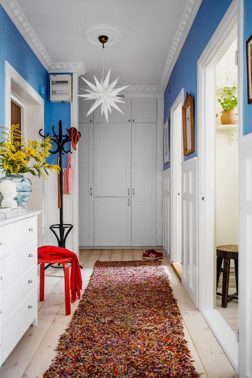 Stuckaturer och platsbyggda paneler får den lilla lägenheten att kännas mer som en våning. På kortsidan i hallen ryms både förvaring, kyl och frys.