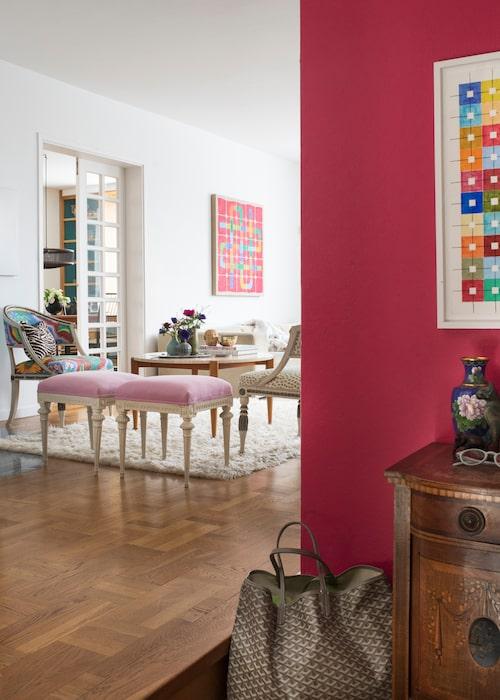 En knallrosa väggfärg välkomnar besökare i hallen. De gustavianska fåtöljerna och taburetterna är omklädda i nya tyger som följer upp färgglädjen, av bland annat Josef Frank, som även formgivit soffbordet med skiva av travertin.