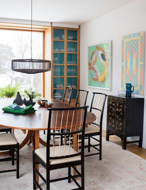 """Matbordet och de gracila matstolarna är signerade Josef Frank. Vitrinskåpen som ramar in det stora fönstret har platsbyggts och insidan är målad i """"sophiegrönt""""."""