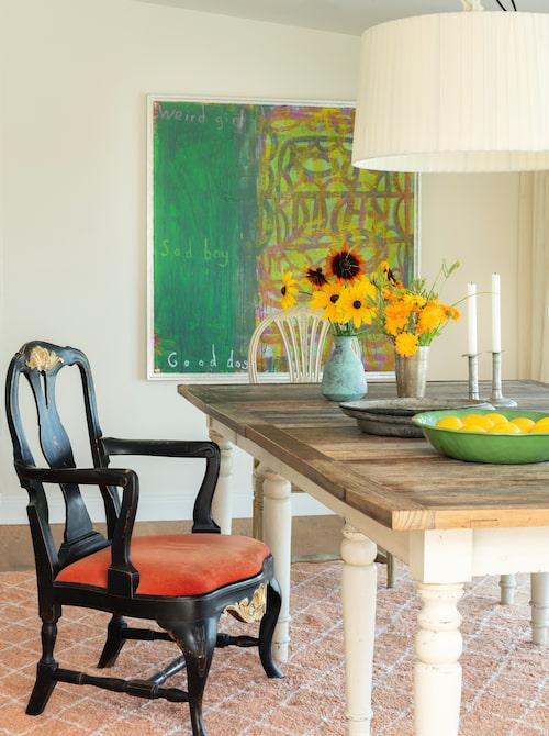 Matsalsbordet är nytillverkat, från Artwood, men stolarna är omklätt arvegods. Berbermatta från Knut, taklampa med tygskärm från gamla R.o.o.m. Grön oljemålning av Lukas Göthman. På bordet spansk keramikskål, solrosor i vas från Posh living, vasen med ringblommor och tennljusstakarna är ärvda.