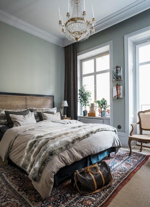 I parets hem blandas högt och lågt, billigt och dyrt. Sänggavel från Jotex, karmstolen är ett arvegods från Calles mormor, förvaring från Louis Vuitton. Pälspläd, H&M Home.