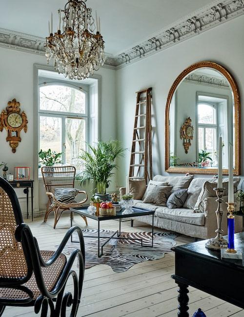 Vardagsrummet andas kolonialstil. Den generösa spegeln, ett arvegods, gör rummet visuellt större och reflekterar dessutom ljuset utifrån. Soffa, Posh living, soffbord från Familjen Fogelmarck, koskinn  med zebratryck, Zara home.