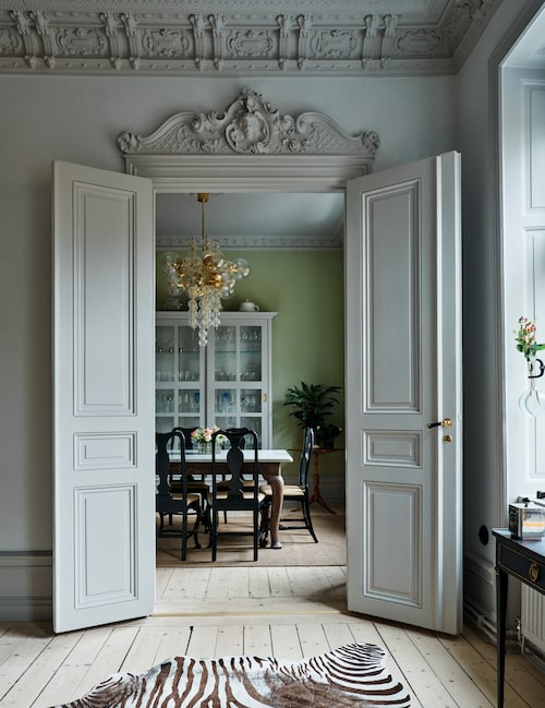 Pampiga dubbeldörrar bjuder in till köket, vardag såväl som fest. Matbordet är arvegods från Calles mormor. Taklampan, italienskt 60-tal, är ett auktionsfynd från Bukowskis.