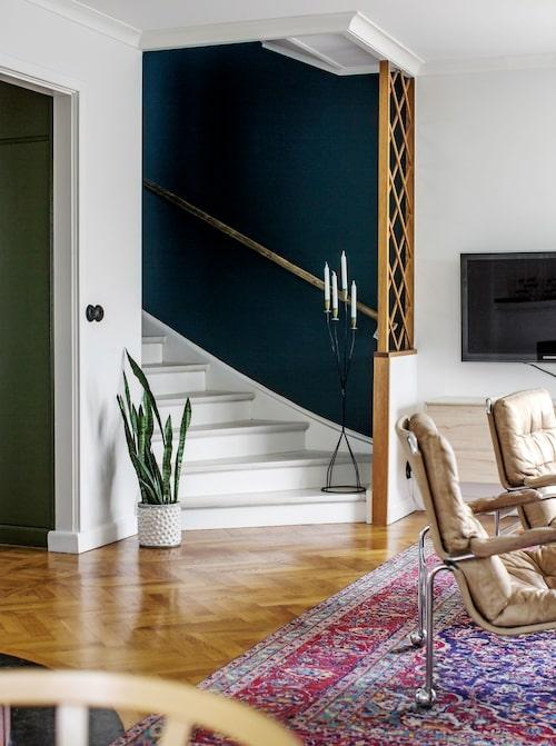 Inga gardiner men gröna växter i överflöd som mjukar upp i vardagsrummet. Spaljén i trappan är en originaldetalj. Ljusstaken kommer från butiken Majornas saker från förr. Bruno Mathssons Karinfåtöljer står på en persisk matta köpt på Lauritz.com.