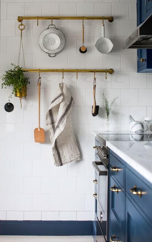 Köksredskap i gammal stil gör sig fint mot den vita kakelväggen. Hänglisten i mässing är från Byggfabriken.