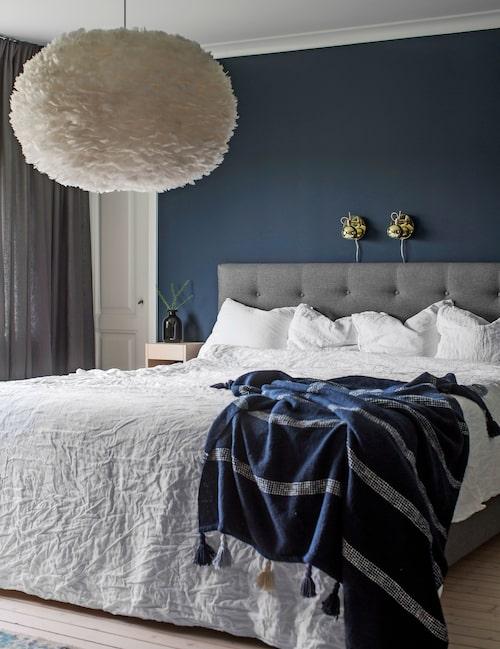 Den mörka färgsättningen går igen i sovrummet. Blå kulör Smoking från Alcro. Säng från Mio, sängbord Norrgavel, bäddset från Ellos, filt från Lagerhaus. Taklampa Eos, Rum21, och sänglampor från Ellos.