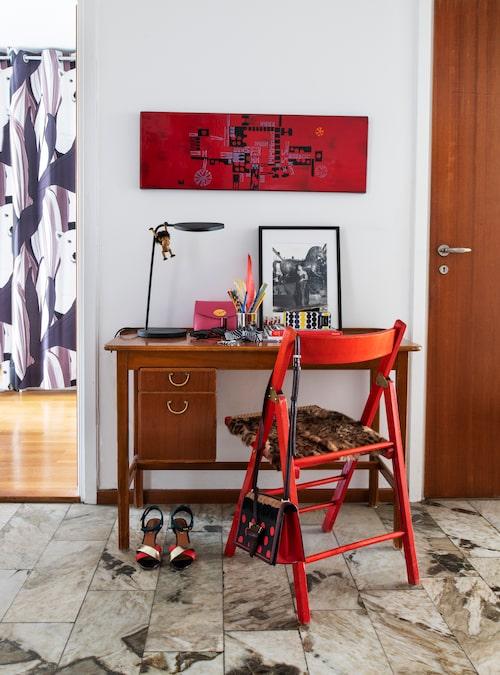 Det lilla skrivbordet är köpt på Jacksons och är det första som möter ögat i hallen. Den ärvda rödmålade lackstolen med rottingsits lyser upp. Till vänster skymtar sonen Gordons rum och ett draperi med isbjörnar från Marimekko.