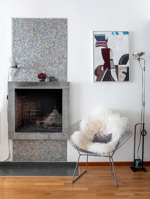 """Spisen är original i sann funkisstil, men mosaiken har Katharina satt upp. Bertoias Diamond chair mjukas upp av en fårskinnsfäll. I stolen ligger en Gos-kudde i grå sammet med spiknitar. Ett """"funproject"""" Katharina har med kollegan och vännen Susanna Wendt. Golvlampan är Castiglionis Toio. Målning av C E Bodén."""