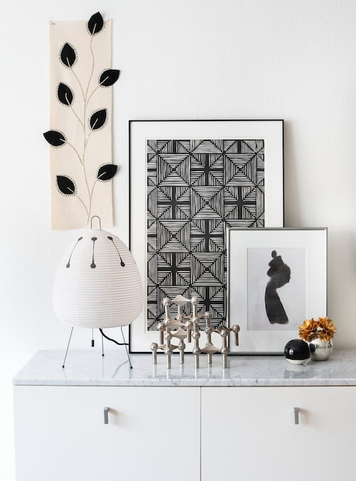 Ett stilleben i svartvitt med föremål och konstverk som Katharina arrangerat smakfullt. Lampan är från Vitra. Bladrankan är en stygnövning Katharina gjorde på Handarbetets vänner.