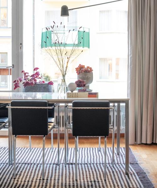 Matbordet består av en lackad laminatskiva som vilar på måttbeställda metallben. Stolarna är designade av Gunilla Allard, från Nordiska galleriet. Matta, David design.